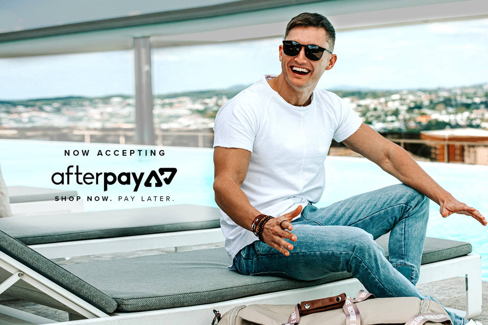 Guy sitting by the pool with duffle bag - Afterpay