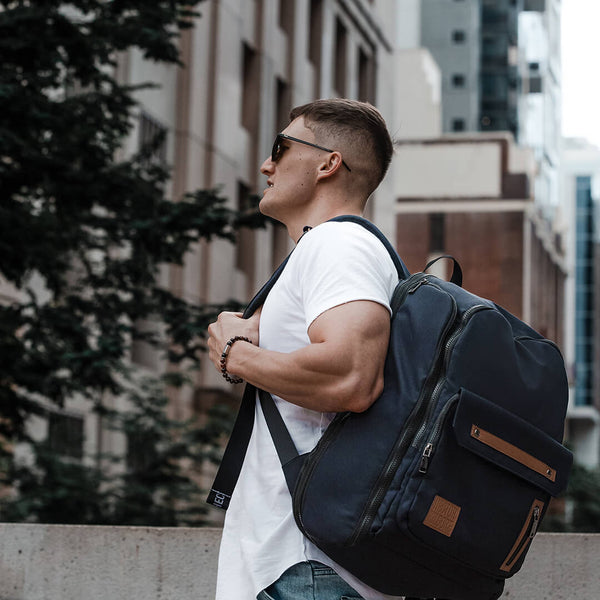 Man wearing Black backpack work bag laptop bag travel bag gym bag carry on recycled