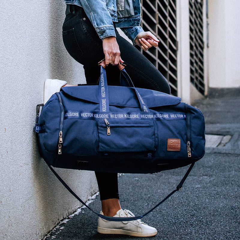 Women with navy blue duffle travel bag in city