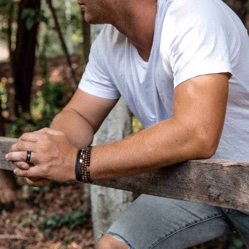 Man wearing black and silver tungsten ring and leather and beaded bracelets