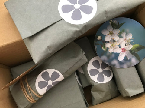 Customer orders wrapped in grey tissue paper and with a Ginger Mint reelable sticker to secure