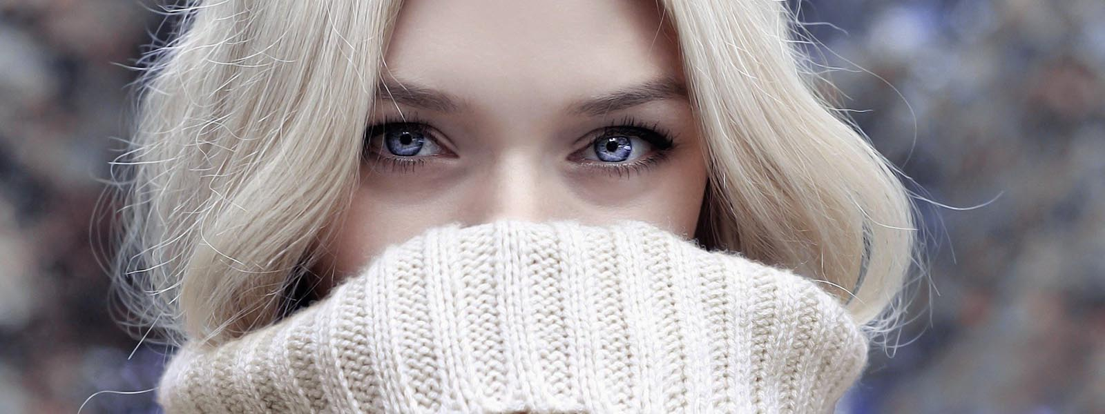 Woman's face hiding in winter scarf
