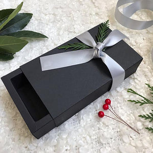Open black box with silver ribbon and natural foliage