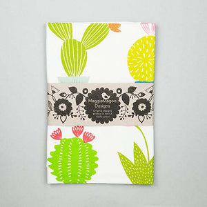 Folded white tea towel with large bright coloured cacti and succulent design made by Maggie Magoo Designs