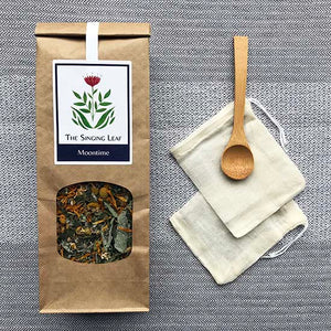 Loose Moomtime herbal tea with a bamboo spoon and two reusable cotton tea bags