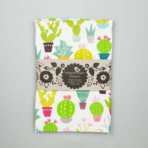 Folded white tea towel with small bright coloured cacti and succulent design made by Maggie Magoo Designs