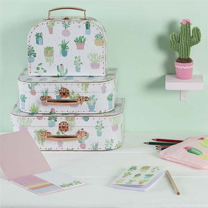 Set of 3 suitcases with pastel cactus design in a home office