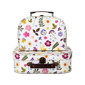 A pair of nesting suitcases with a pressed flower design