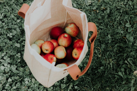 Fabric grocery bag filled with apples on grass.