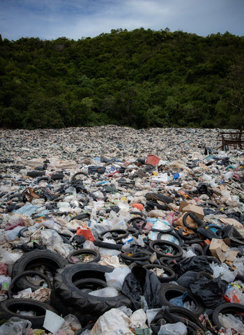 Scene of plastic bags and tyres in landfill covering the ground.