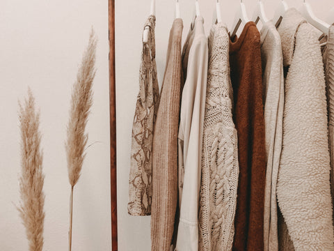 Brown and beige coloured clothing on rack with plant to the side.