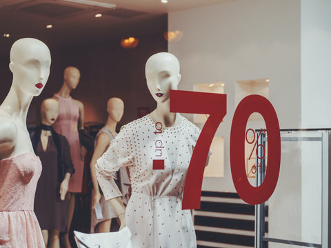 White and pink dressed mannequin in shop window with 'up to 70% off' written on window.