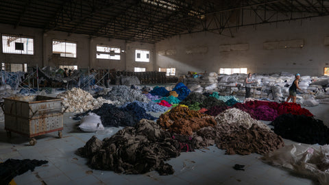 Large piles of unwanted clothes on the floor of a factory for sorting.