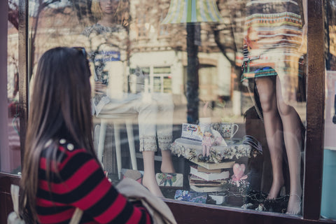Woman looking in shop window at clothes.