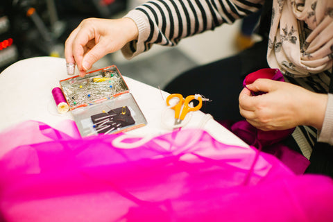 Seamstress at work. Women's hands holding sewing needle and pin, working on a bright pink fabric.