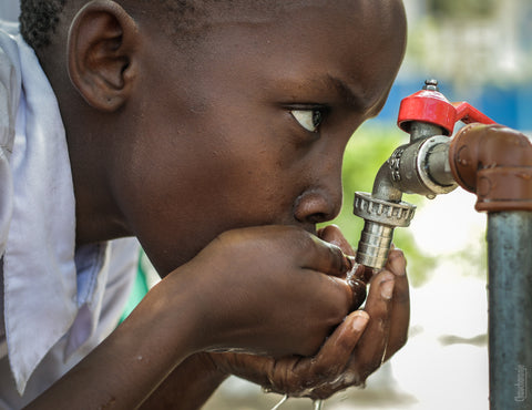 Boy drinking water from playground faucet