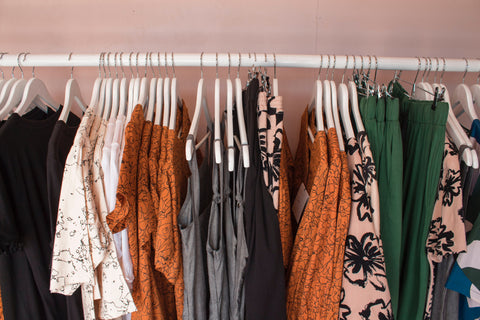 Women's blouses on a clothing rack against a pink wall.
