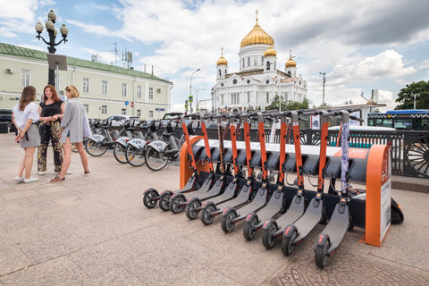 Orange and grey scooters held in a rack in the middle of a city.