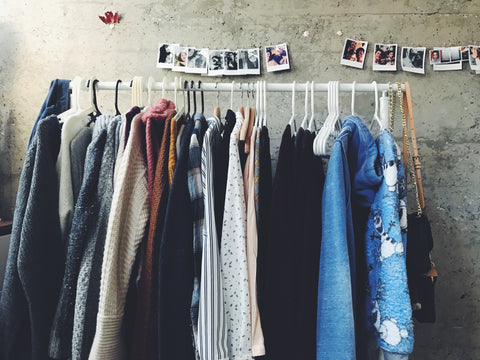 Assorted colour clothing on white rack with polariod pictures behind on concrete wall.