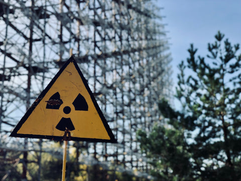 Hazard sign with metal structures in the background.