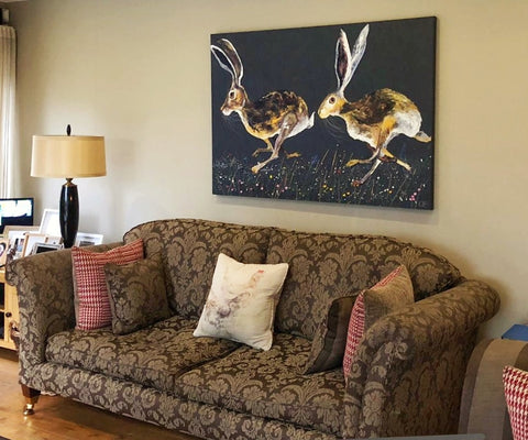 Quinn Russell painting above a sofa in customers home. Two hares running on canvas
