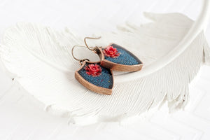 side view of teal and coral flower earrings