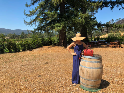 Model standing near barrel at Chateau St. Jean in Sonoma with Post Bag on barrel.
