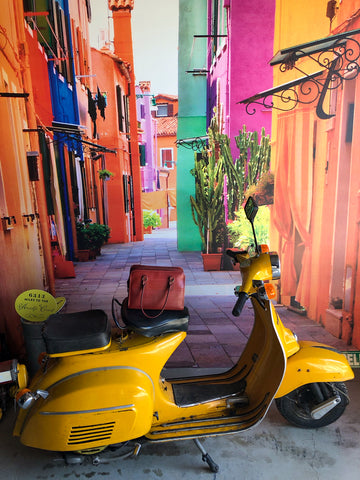 Post Bag on yellow scooter in front of wall that shows picture of Italian street