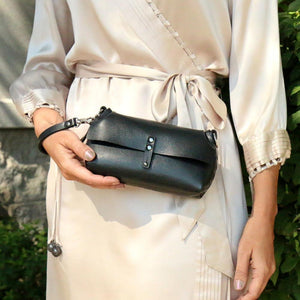 Ebony (Black) wristlet with shoulder strap to double as crossbody.  Hand riveted together with black rivets and silver hard wear.  This is a small bag the holds just the essentials and has a button closure in front.  Detachable wristlet strap.  Worn on wrist of model in off white silk dress