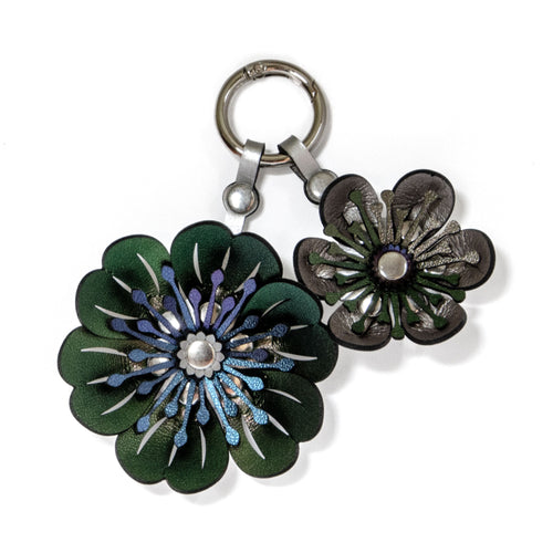 Two flower purse charm with silver metal hard wear loop to attach to bags.  Flowers are multi-colored made of iridescent, vegan leather fabric and riveted together with silver rivets.