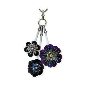 Three flower purse charm with silver metal hard wear loop to attach to bags.  Flowers are multi-colored made of iridescent, vegan leather fabric and riveted together with silver rivets.