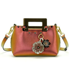 Load image into Gallery viewer, Front of small ruby iridescent vegan leather purse with black rectangular acrylic handles.  Purse is riveted together with dark silver rivets and gold hard wear.  Top snaps closed and has detachable strap to wear as crossbody or shoulder bag.  Has small loop of fabric on front upper right to hold purse charm.  Shows silver, black and ruby two flower purse charm attached.  Available for purchase at sadieanddaisy.com