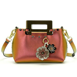 Front of small ruby iridescent vegan leather purse with black rectangular acrylic handles.  Purse is riveted together with dark silver rivets and gold hard wear.  Top snaps closed and has detachable strap to wear as crossbody or shoulder bag.  Has small loop of fabric on front upper right to hold purse charm.  Shows silver, black and ruby two flower purse charm attached.  Available for purchase at sadieanddaisy.com