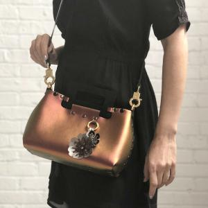 Front of small ruby iridescent vegan leather purse with black rectangular acrylic handles and two flower purse charm worn by model in black dress as crossbody.  Purse is riveted together with dark silver rivets and gold hard wear.  Top snaps closed and has detachable strap to wear as crossbody or shoulder bag.  Has small loop of fabric on front upper right to hold purse charm.  Available for purchase at sadieanddaisy.com