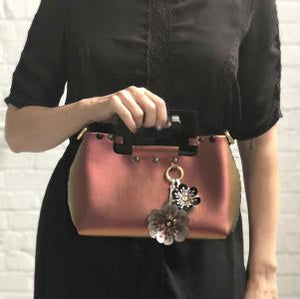 Front of small ruby iridescent vegan leather purse with black rectangular acrylic handles and two flower purse charm held by acrylic handles by model in black dress.  Purse is riveted together with dark silver rivets and gold hard wear.  Top snaps closed and has detachable strap to wear as crossbody or shoulder bag.  Has small loop of fabric on front upper right to hold purse charm.  Available for purchase at sadieanddaisy.com