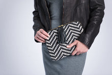 Load image into Gallery viewer, Held by female model in gray dress and black leather jacket.  Front of Kavya Clutch Black and Gray.  This clutch supports girls' education in India.  It is rectangular with zip closer and black leather tassels attached to zip closer.  The bag is made of woven cotton fabric with black and gray lines that make a chevron patter.