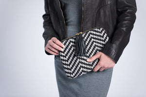 Held by female model in gray dress and black leather jacket.  Front of Kavya Clutch Black and Gray.  This clutch supports girls' education in India.  It is rectangular with zip closer and black leather tassels attached to zip closer.  The bag is made of woven cotton fabric with black and gray lines that make a chevron patter.
