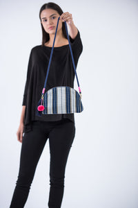 Front of Half Moon Crossbody or clutch is handmade in India and supports girls education.  Held up by female model in black pants and shirt.  It is woven fabric with white and blue stripes and a blue rope strap the is removable.  The bag has a pink pom pom bag charm and a blue tassel.