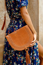Load image into Gallery viewer, Structures crossbody saddle bag in tan leather with snap closer and hoop with tan leather tassel hanging off bottom.  Front has detail of woven leather in line just in from edge of front flap.  Over shoulder of model in blue dress with flower pattern.