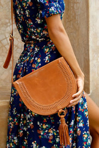 Structures crossbody saddle bag in tan leather with snap closer and hoop with tan leather tassel hanging off bottom.  Front has detail of woven leather in line just in from edge of front flap.  Over shoulder of model in blue dress with flower pattern.