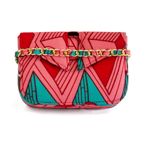 Front of small box bag with split flap front to be used as a clutch or shoulder bag.  Shows gold chain strap with fabric woven though it.  Made with bright pink, red and teal Ankara fabric in Nigeria.