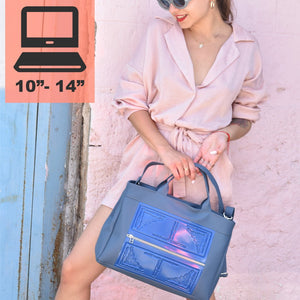 Asia crossbody front of work bag/tote in blue with embossed pattern and handles.  Held by top handles by model in light pink dress.  Has strap to carry as crossbody and fits computer.