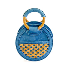 Load image into Gallery viewer, Back of micro handbag that can be worn as a crossbody with detachable strap.  Bag is round and made of indigo dyed denim and bottom half of front and back have rattan, one side with a small pocket.  Zipper closure on top with wooden round handles partial covered with denim so bag can be held as a handbag.