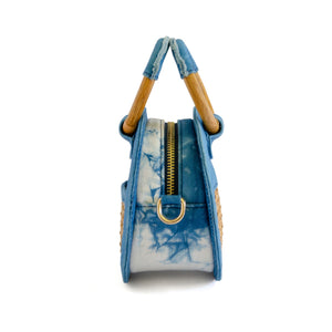 Side of micro handbag that can be worn as a crossbody with detachable strap.  Bag is round and made of indigo dyed denim and bottom half of front and back have rattan, one side with a small pocket.  Zipper closure on top with wooden round handles partial covered with denim so bag can be held as a handbag.
