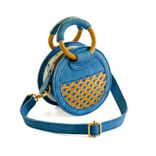 Load image into Gallery viewer, Front of micro handbag that can be worn as a crossbody with detachable strap.  Bag is round and made of indigo dyed denim and bottom half of front and back have rattan, one side with a small pocket.  Zipper closure on top with wooden round handles partial covered with denim so bag can be held as a handbag.