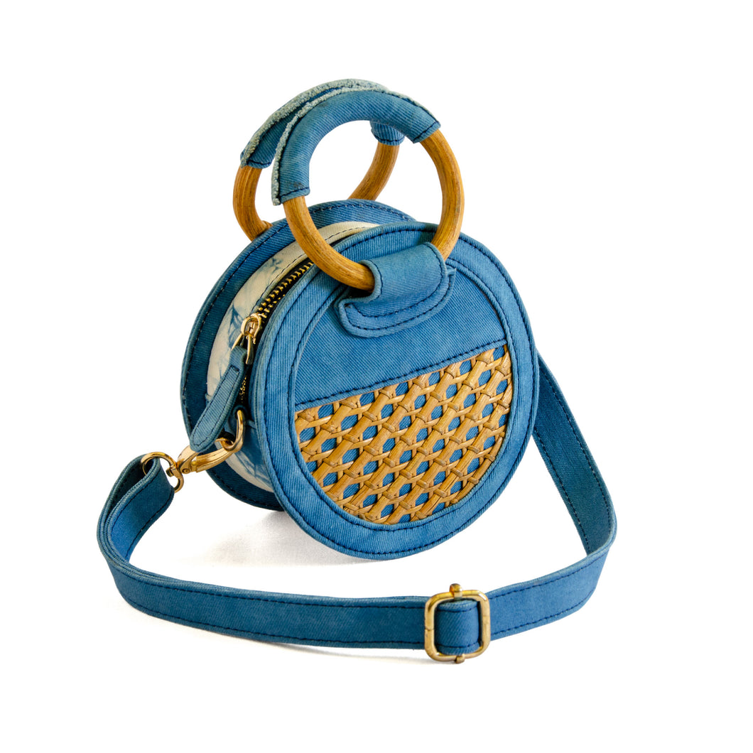 Front of micro handbag that can be worn as a crossbody with detachable strap.  Bag is round and made of indigo dyed denim and bottom half of front and back have rattan, one side with a small pocket.  Zipper closure on top with wooden round handles partial covered with denim so bag can be held as a handbag.