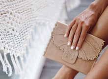 Load image into Gallery viewer, Front of Calypso tri fold wallet in beige leather with scalloped edges and riveting.  Held by hand of model with white nail polish.  Features intricate cut out pattern, flap front.