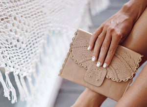 Front of Calypso tri fold wallet in beige leather with scalloped edges and riveting.  Held by hand of model with white nail polish.  Features intricate cut out pattern, flap front.