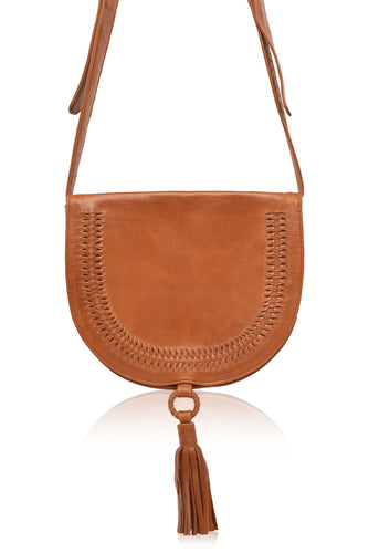 Structures crossbody saddle bag in tan leather with snap closer and hoop with tan leather tassel hanging off bottom.  Front has detail of woven leather in line just in from edge of front flap.