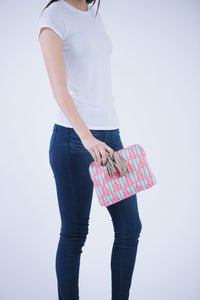 Female model in white t-shirt and jeans holding Kavya Clutch Aqua.  This clutch is rectangular with a zip closer and two leather beige/off white tassels.  The clutch is made from woven cotton that is white with aqua stripes and has pink circle embroidery that makes a triangle pattern.  This bag supports girls education in India.